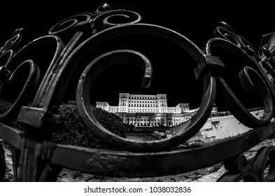 The Parliament House in Bucuresti, Romania, seen at the night through the fence.