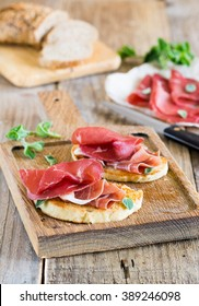 Parma ham  Jamon. Slices of bread roasted with spanish Serrano ham served as tapas. Slices of Prosciutto on the wooden background.