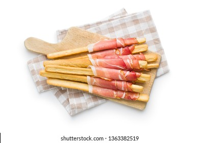 Parma ham prosciutto with grissini breadsticks on cutting board isolated on white background.