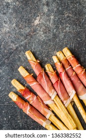 Parma ham prosciutto with grissini breadsticks on old kitchen table.