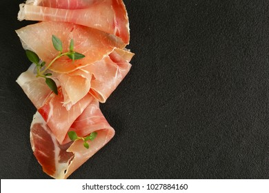 Parma ham thin slices on a black stone