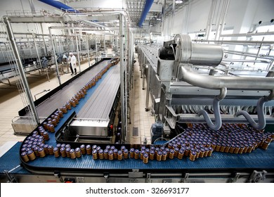 PARMA, ITALY - 3 OCTOBER 2012: Sealed jars of pasta sauce travelling along a conveyor belt at a sauce packaging plant.