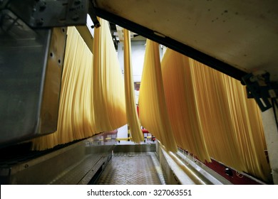 PARMA, ITALY - 3 OCTOBER 2012: Strands of spaghetti move through the production line inside a pasta factory.