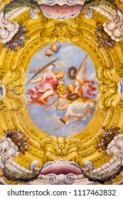 PARMA, ITALY - APRIL 17, 2018: The fresco of angels with the symbols of the martyrdom on the wault of church Chiesa di Santa Lucia by Alessandro Baratta from 17. cent.