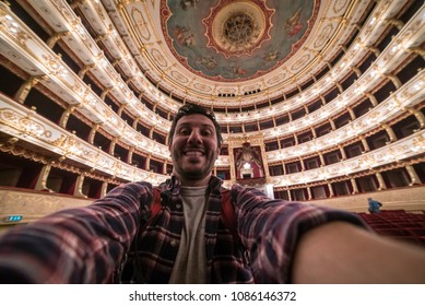 Parma, Italy - October 02, 2011: Happy tourist take selfie photo inside the Teatro Regio of Parma, the opera house and opera company in the city of Parma, Italy