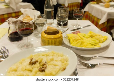 PARMA, ITALY - SEPTEMBER 23, 2012 - Dinner table at an Italian restaurant with pasta, red wine and Parmesan cheese in Parma circa September 2012.