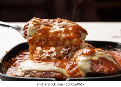 Parmegiana Steak also known as Filet Parmegiana in a black iron pan on a wooden white background, cheese and tomato sauce. Soft light, angle view