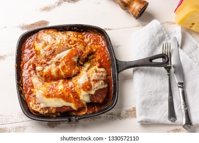 Parmegiana Steak also known as Filet Parmegiana in a black iron pan on a wooden white background, cheese and tomato sauce. Soft light, top view