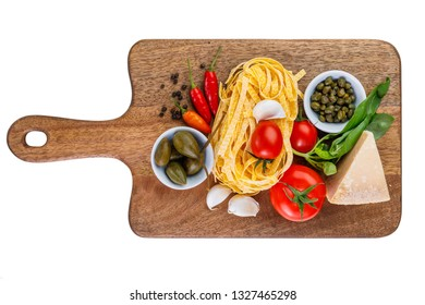 Parmesan, capers, tomato, garlic, basil, chili paprika, pepper and tagliatelle pasta on wooden cutting board isolated on white background. Ingredients for healthy italian lunch or dinner