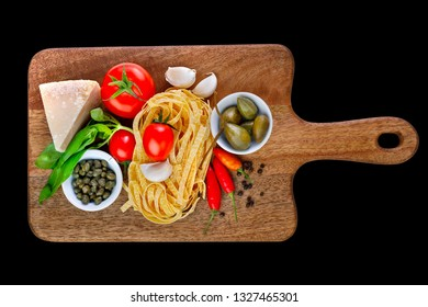 Parmesan, capers, tomato, garlic, basil, chili paprika, pepper and tagliatelle pasta on wooden cutting board isolated on black background. Ingredients for healthy italian lunch or dinner