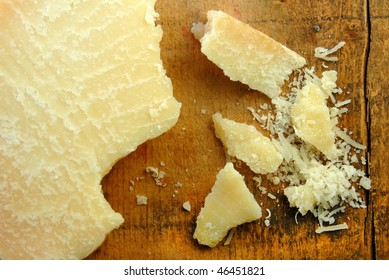 Parmesan cheese in chunks and freshly grated on a rustic wood surface.
