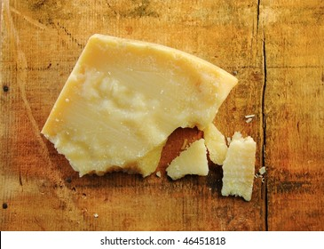 Parmesan cheese chunks on a rustic wood surface.