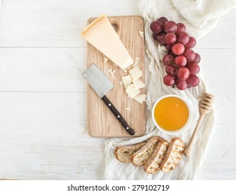 Parmesan cheese with grapes, honey and bread slices on wooden chopping board over rustic white background. Top view, copy space