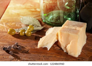 parmesan cheese and green olives with other spices on wooden surface