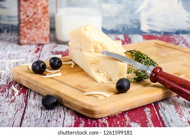 Parmesan cheese with cheese knife on a textured table close-up.