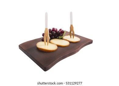 Parmesan cheese on serving board with cluster of grapes and wooden fork