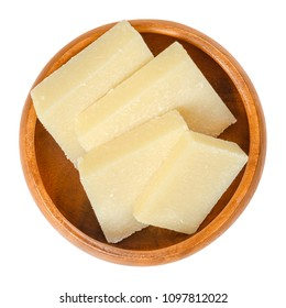 Parmesan cheese pieces in wooden bowl. Parmigiano-Reggiano. Italian hard, granular cheese, of slightly yellow color, made of unpasteurized cow milk. Macro food photo, closeup, from above, over white.