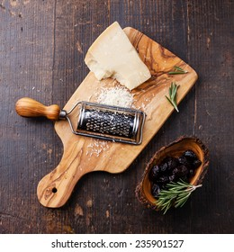 Parmesan cheese and sun-dried olives on olive wood cutting board