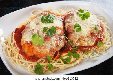 Parmesan chicken with melted cheese, tomato sauce and spaghetti pasta