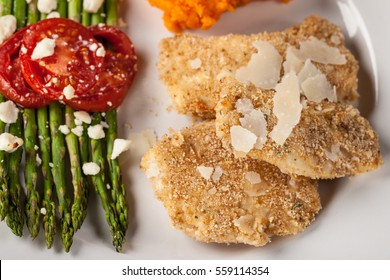 Parmesan Crusted Chicken Tenders with Roasted Sweet Potato and Roasted Asparagus topped with Campari tomatoes, Feta Cheese, Olive oil, and salt on a dark wooden background macro shot