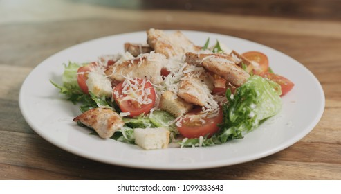 parmesan flakes falling on caesar salad