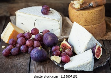 Parmesan and Pont-l'Eveque cheese with with figs and grapes over old wooden table