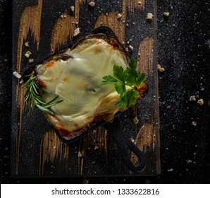 """""""Parmigiana di melanzane"""" (Aubergine parmigiana) over a parmesan cheese  decorated with fresh basil  on pots. moussaka witheggplant, beef and tomato sauce"""