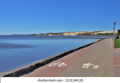 Parnidis Dune in Nida in the background. Bike lanes, cycle lane, bikeways, cycleway, lanes, roadway for cyclists and pedestrians in Nida, resort town near Curonian Spit, Lithuania, Baltics. Relaxation