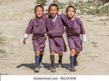 PARO, BHUTAN - CIRCA OCTOBER 2012: three school kids in traditional bhutan outfit walking together