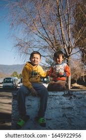 PARO, BHUTAN - January 14, 2020 : Unidentified Bhutanese boys sit on the wall and pose for a photo shoot.