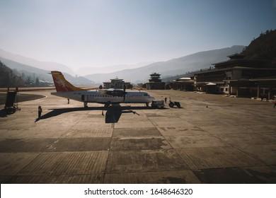 PARO, BHUTAN - January 14, 2020 : View of Paro international airport, Bhutan with Druk Air's plane is parking. Paro international airport is the airport that surrounded by mountains.
