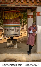 Paro, Bhutan - March 28, 2018 : A Bhutanese tourist guide waiting at the Dungtse temple for his guests to return, standing next to a big prayer wheel.
