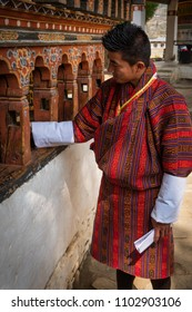 Paro, Bhutan - March 28, 2018 : A Bhutanese man in traditional dress turning the prayer wheels at Dungtse Temple in Paro