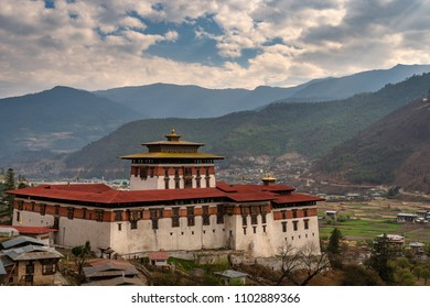 Paro, Bhutan - March 29, 2018 : View on the Paro Dzong with the Himalayas in the background