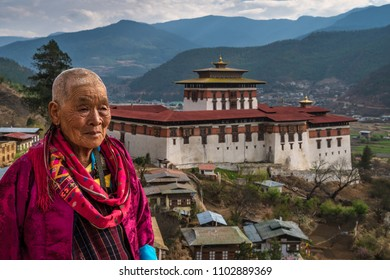 Paro, Bhutan - March 29, 2018 : Old woman going home from the Paro festival at the end of the day, with in the background the Paro Dzong