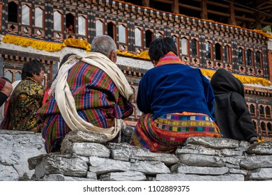 Paro, Bhutan - March 29, 2018 : Attendees of the annual Paro festival sitting at the tribune made from natural stone