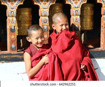 PARO, BHUTAN - NOVEMBER 06,2012 : Unidentified smiling young monks standing by the religious prayer wheels at Paro Rinpung dzong, Paro, Bhutan