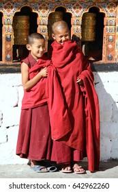 PARO, BHUTAN - NOVEMBER06,2012 : Unidentified smiling young monks standing by the religious prayer wheels at Paro Rinpung dzong, Paro, Bhutan