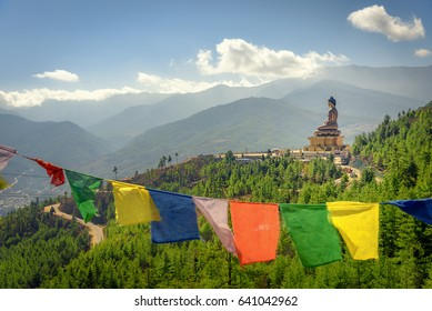 Paro Buddha with prayer flags in foreground and the valley in the background
