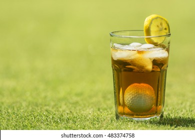 Parody combining iced tea in a glass with a golf ball and tee