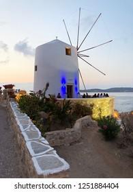 Paros - August 29, 2018: Traditional cycladic windmill on sunset. Parikia, Paros island, Greece