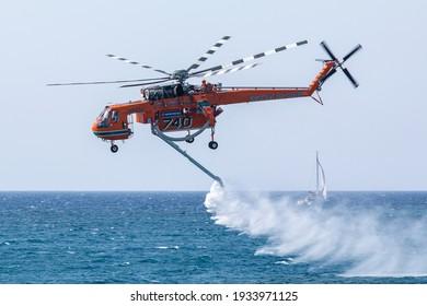 Paros Island, Greece- 26 September 2020: A helicopter of the fire brigade extinguishing a fire off the coast of the Paros island. Sikorsky s-64e skycrane.