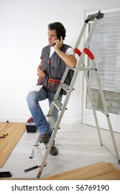 Parquet layer on phone leaning on a ladder