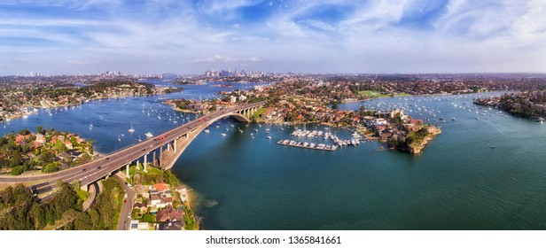 Parramatta river crossed by Gladesville bridge in Sydney Inner West - elevated aerial panorama with view of distant Sydney city CBD skyline and harbour shores.