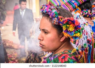 Parramos, Guatemala - December 29, 2016: Local indigenous woman dressed in ceremonial headdress & costume participates in religious ceremony in village near UNESCO World Heritage Site of Antigua.