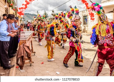 Parramos, Guatemala - December 29, 2016: Marimba musicians & traditional folk dancers in masks & costumes perform Dance of the Moors in village near UNESCO World Heritage Site of Antigua.