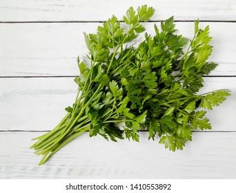Parsley bunch on wooden table background. Fresh raw parsley plant top view. Organic italian parsley closeup on rustic white wood, vegetarian food cooking ingredient. Petroselinum parsley herb flat lay