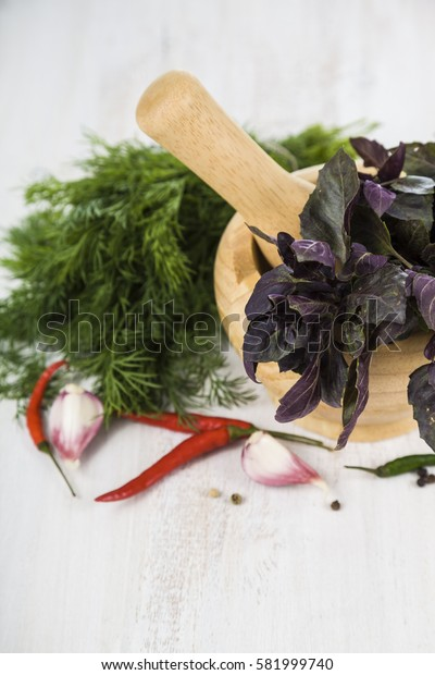 Parsley, dill and basil on a light wooden background. Spices and herbs in a wooden mortar to prepare various dishes.