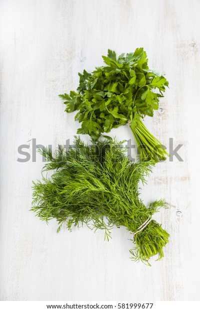Parsley and dill on a light wooden background. Spices and herbs  to prepare various dishes.