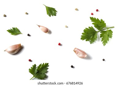 Parsley leave with garlic and colored peppercorns isolated on white background - top view